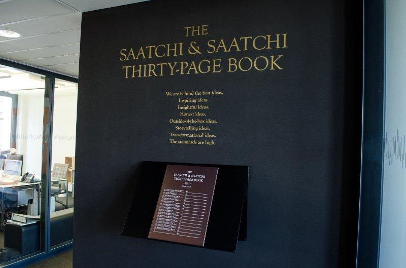 """Foto einer Tafel mit der Aufschrift """"The Saatchi & Saatchi thirty-page book"""" mit den besten Arbeiten des Saatchi & Saatchi Netzwerkes"""
